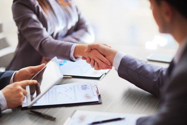 A photo of handshake at the beginning of a business meeting